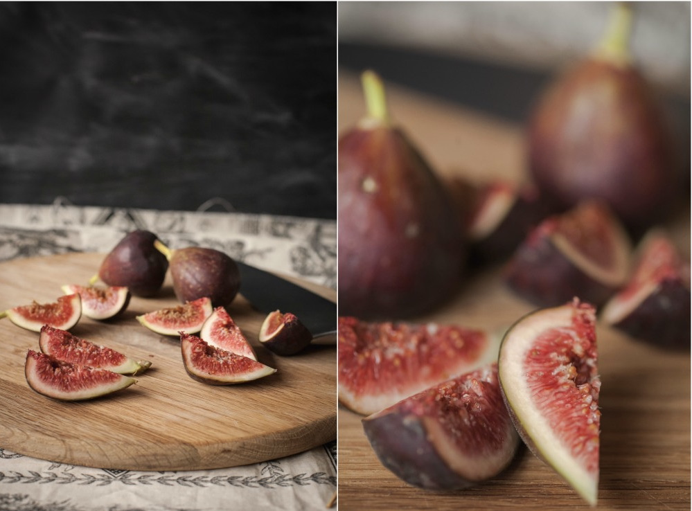 Cut and uncut fresh figs on a wooden cutting board.