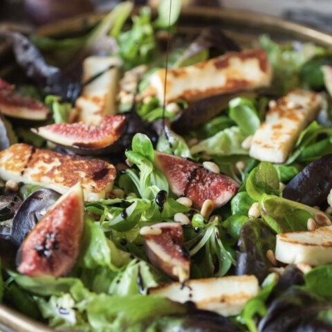 Pomegranate balsamic dressing drizzling on fig and halloumi winter salad