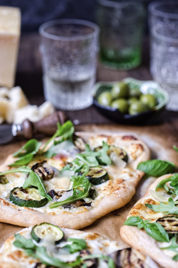 Grilled vegetable pizza with olives and a glass of water