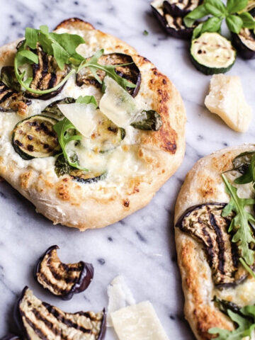 Grilled vegetable pizza bianca next to additional grilled eggplant and cheese
