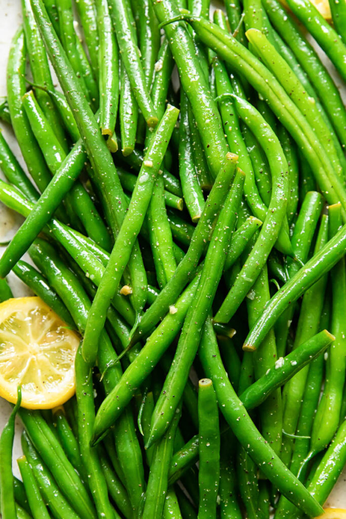 Cooked lemon butter green beans with a slice of lemon