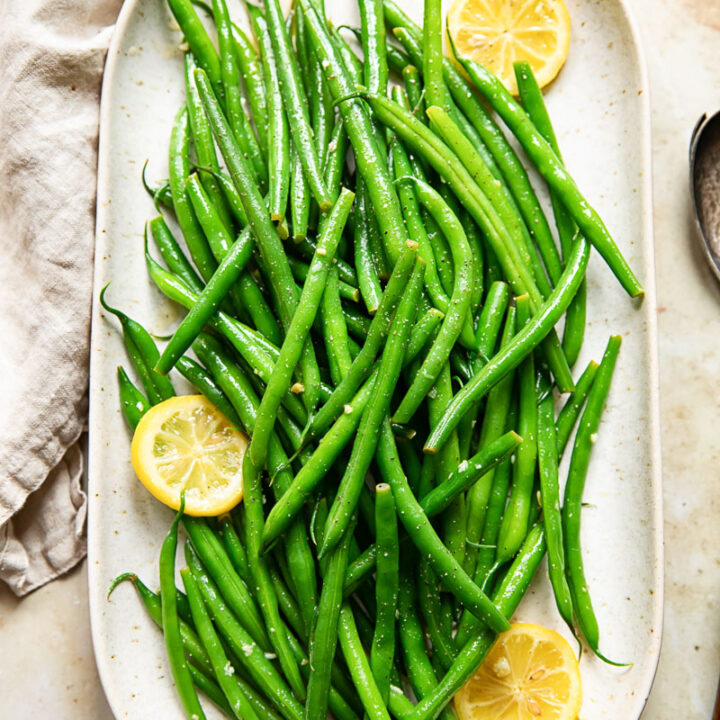Platter of green beans with lemon butter, with visible lemon slices.
