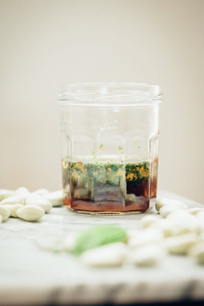 Jam jar with layered ingredients for vinaigrette.