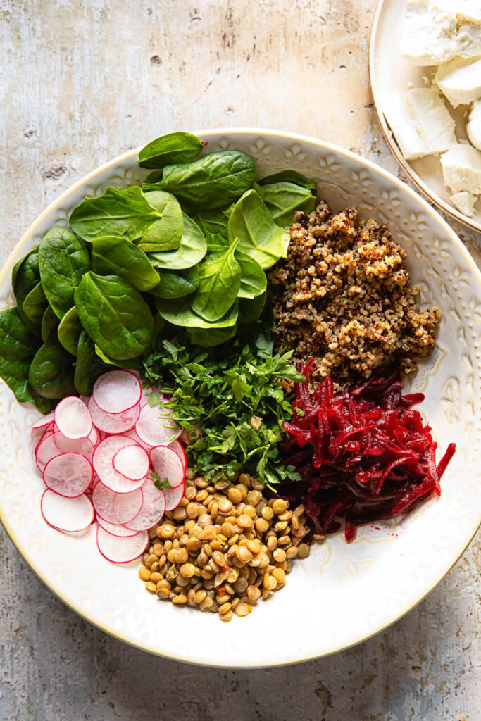 Process shot of quinoa and lentil salad ingredients in a bowl