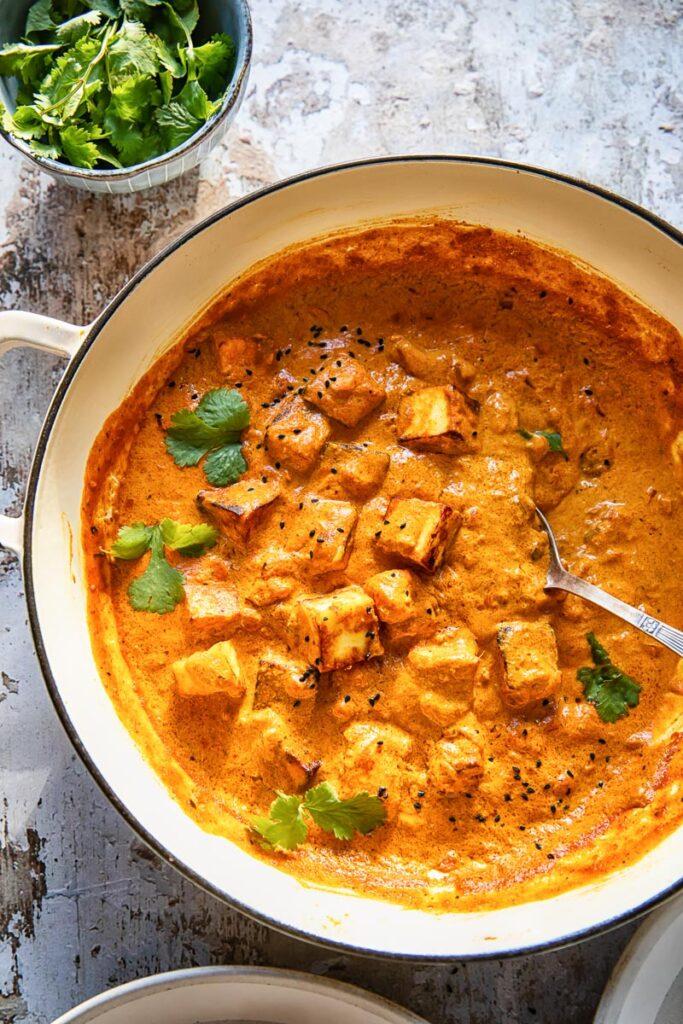 large pan of paneer tikka masala beside bowl of cilantro