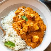 Serving bowl of paneer tikka masala with white rice