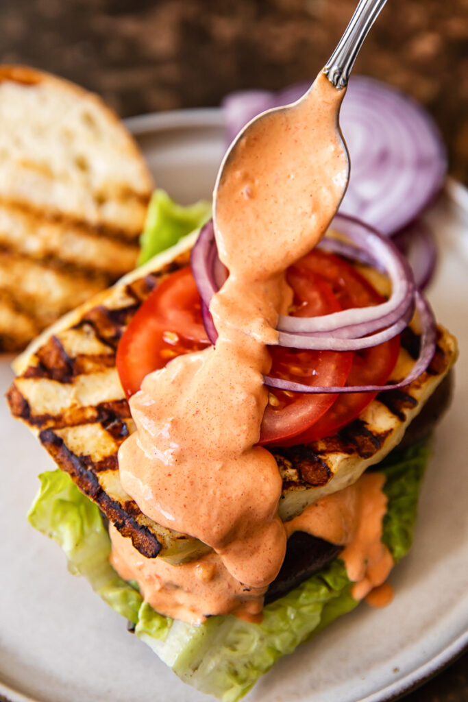 Open grilled halloumi burger with garlic red pepper aioli being added by a spoon