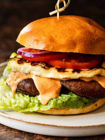 Side view of grilled halloumi burger with garlic red pepper aioli oozing down