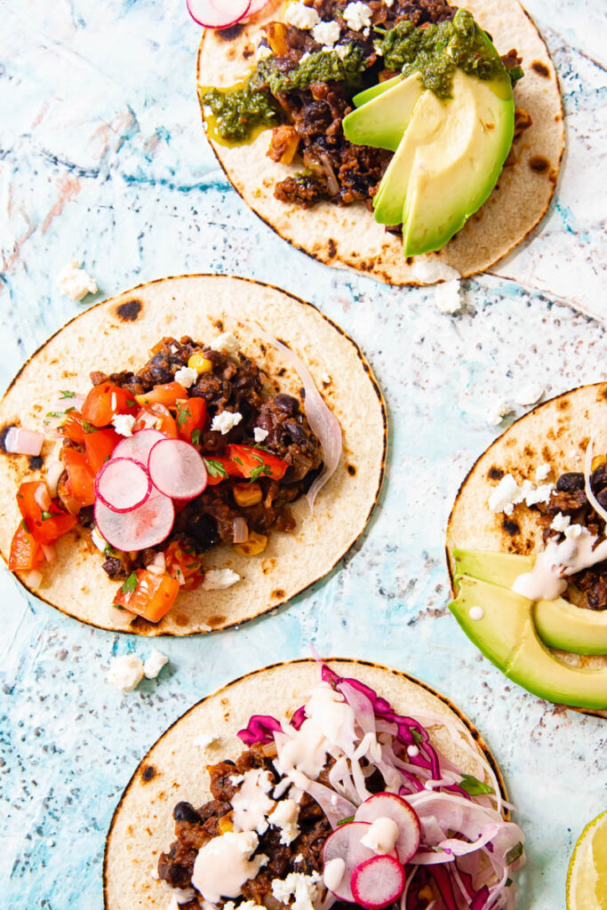 Four tacos on a colourful background with various toppings