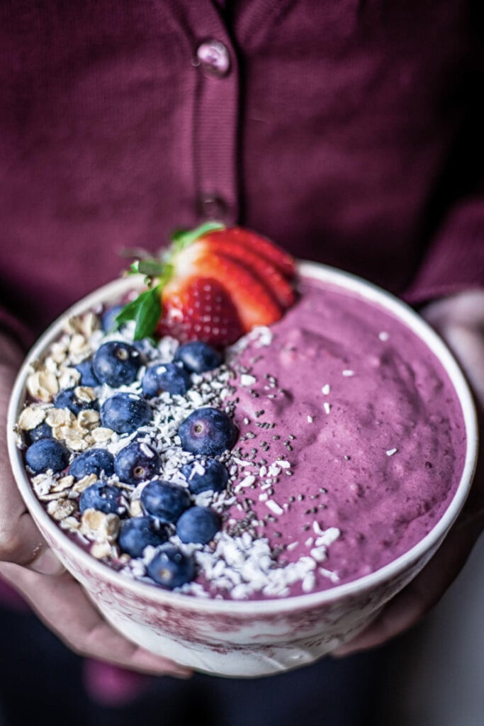 Two hands holding a berry smoothie bowl