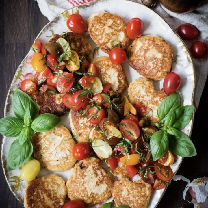 Platter of ricotta pancakes with tomato basil salsa next to extra ingredients on wood table