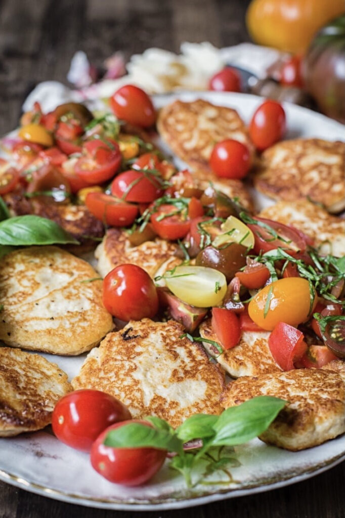 Side view of platter of ricotta pancakes with tomatoes and basil