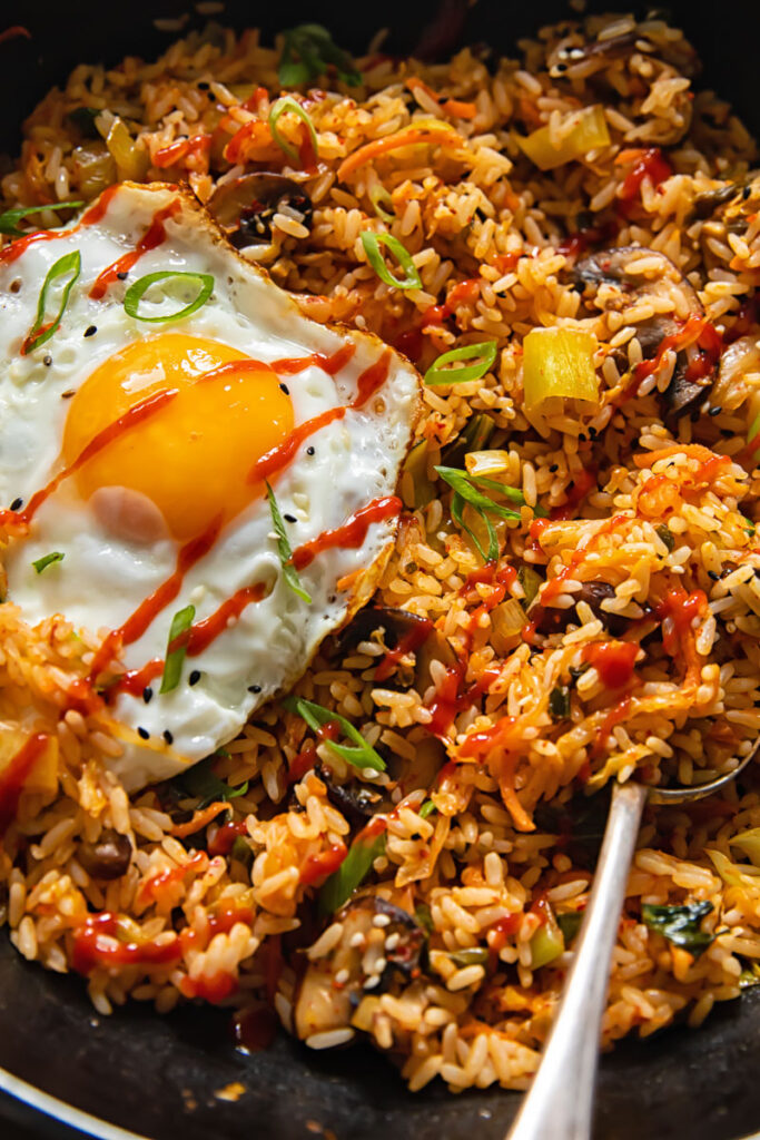 Close up view of kimchi fried rice with an fried egg on top