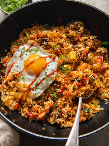 Wok with a spoon in fried rice with a fried egg on top