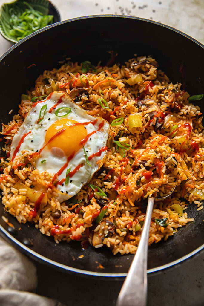 Wok with the final dish showing an egg and a spoon