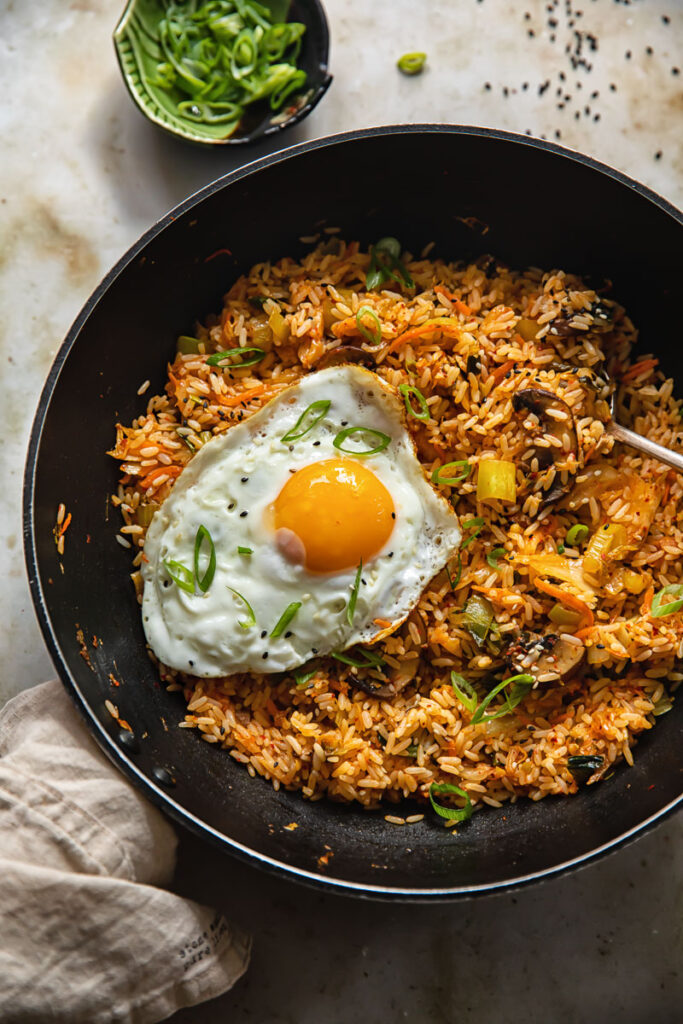 Wok with kimchi fried rice and a fried egg next to a small dish of sliced green onions