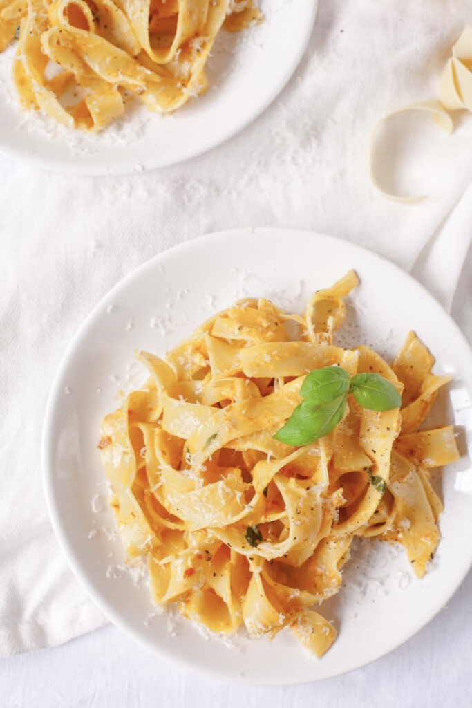 Plate of pappardelle with sun-dried tomato and mascarpone from the top with basil leaf