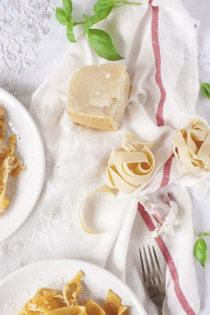 Dried pappardelle on a table with basil and hard cheese
