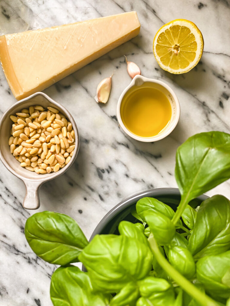 Photo of pesto ingredients, with cheese, pine nuts, lemon, oil, garlic and a basil plant