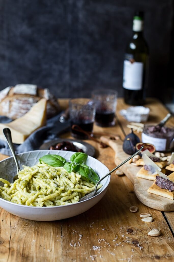 Bowl of pesto pasta with cheese board and wine bottle in the background