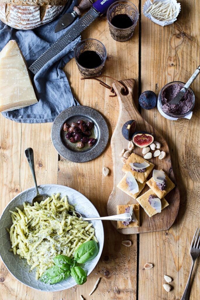 Plate of pesto pasta on a wood table with cheese, bread and olives