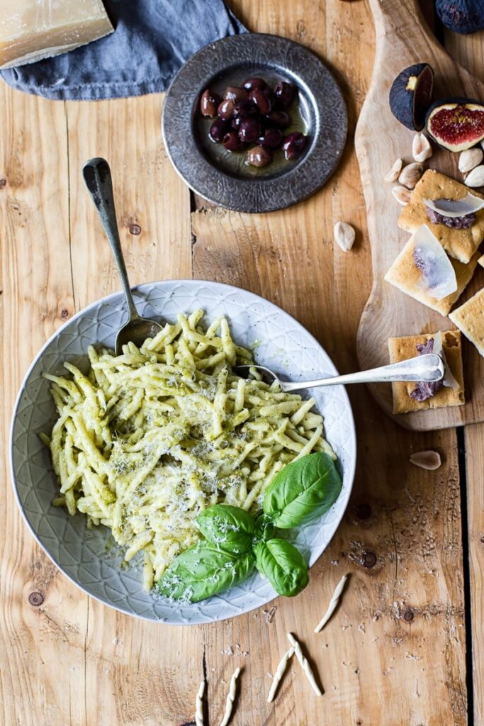 Bowl of pasta on wood table beside olives and cheese board