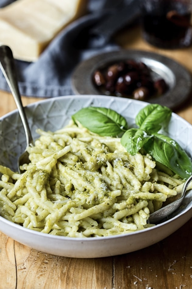 Close up view of pasta with pesto and an additional basil leaf