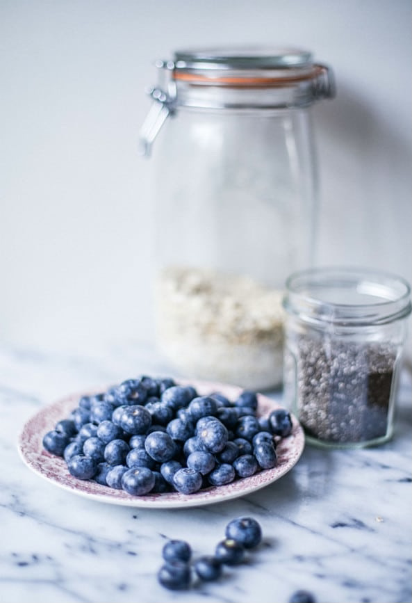 Plate of blueberries in front of two glass jars