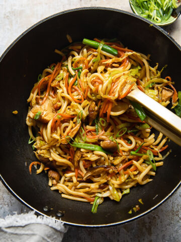 Top down view of a wok with vegetarian yaki udon noodles being stirred