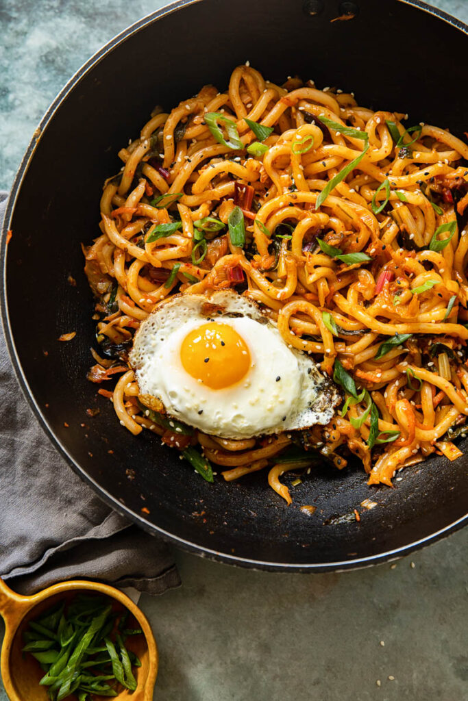 Noodles and a fried egg in a wok style pan