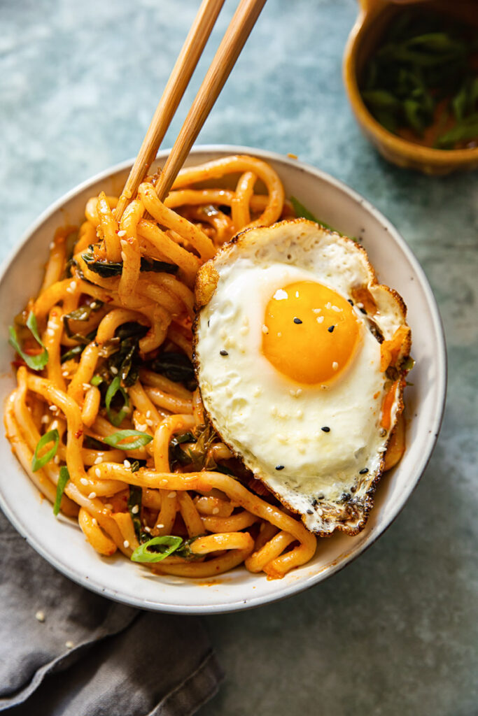 Kimchi noodles in a bowl with a fried egg and chop sticks