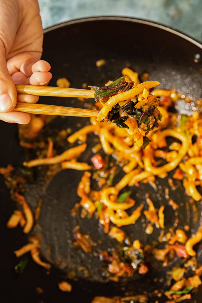 Close up of noodles held by chop sticks