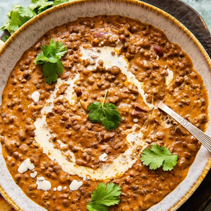 Dal makhani in a bowl with a spoon and leaves of parsley