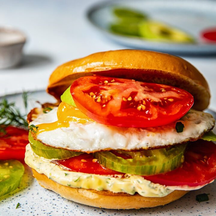 Bagel sandwich with the top angled off and a tomato on top