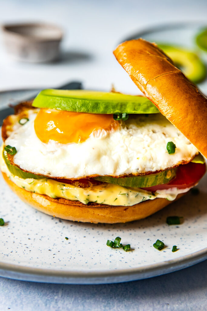 Bagel sandwich with the top askew on a plate