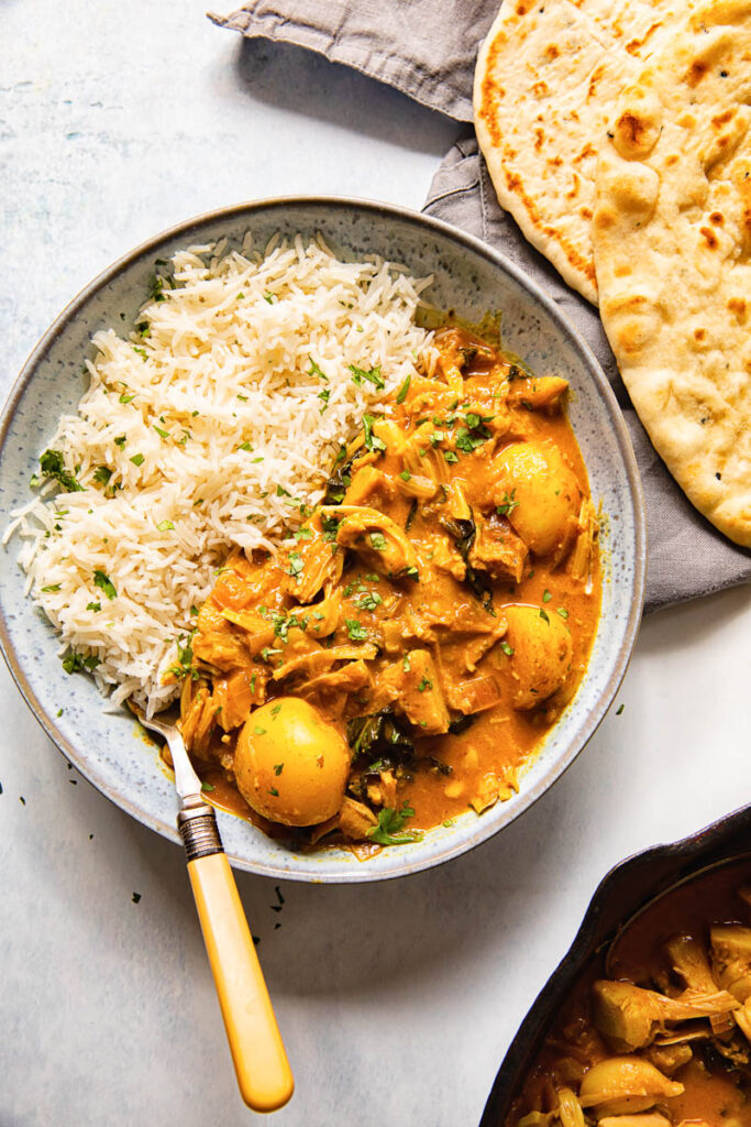Bowl of curry and rice alongside naan