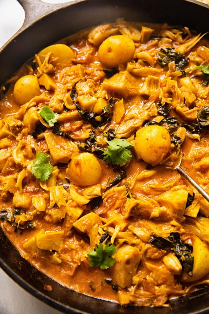 Cast iron pan with jackfruit curry and a serving spoon